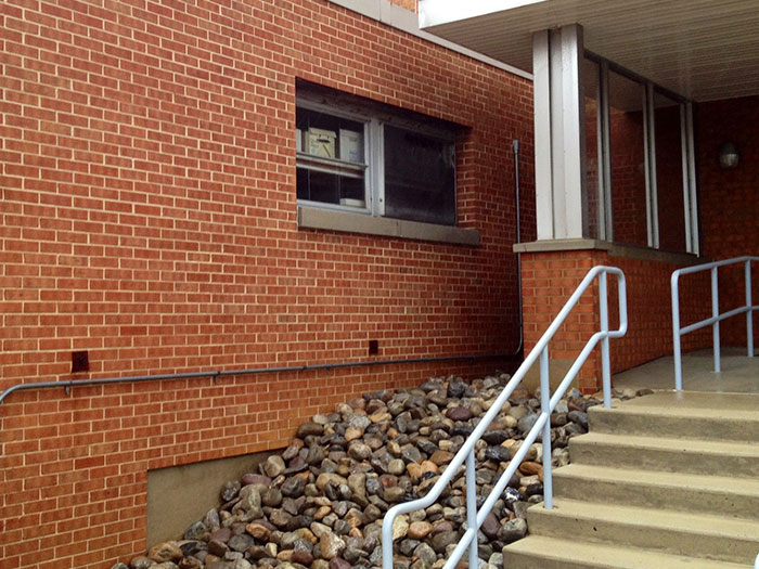 Pressure washed commercial brick apartment building with steps.